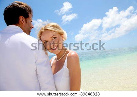 Just-married couple standing by blue lagoon - stock photo