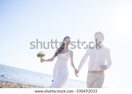 Just married happy couple running on a sandy beach - stock photo