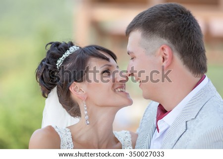 Just married in day of the wedding. Happy newly wedded looking at each other on open air - stock photo