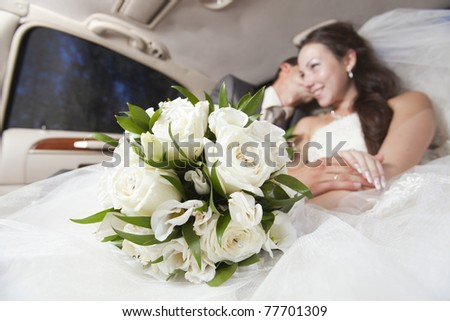 Just married joyful young couple inside limo - stock photo