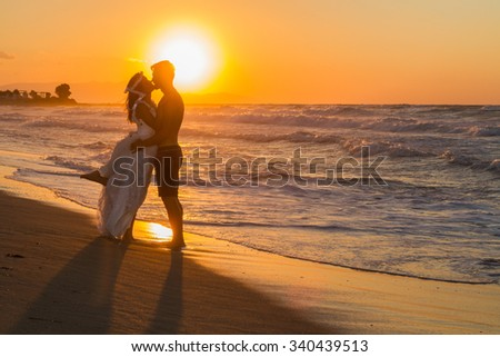 Just married young couple at the beach, enjoying the hazy dusk, wearing a wedding dress and shorts, walking barefoot, getting wet, teasing and kissing one another. - stock photo