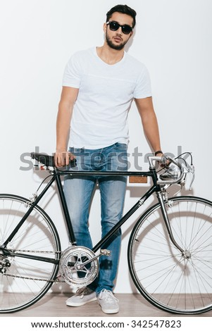 Just me and my bike. Full length of handsome young Indian man in sunglasses leaning at his retro styled bicycle while standing against white background - stock photo