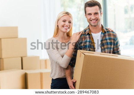 Just moved in. Smiling young man holding a cardboard box while his girlfriend holding hands on his shoulders  - stock photo
