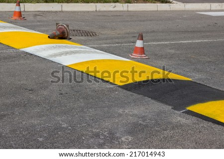 Just painted stripes on a speed bump for slowing traffic near school. Freshly painted speed bump. Selective focus. - stock photo