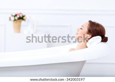Just relax. Content beautiful young woman listening to music and closing her eyes while taking a bath - stock photo