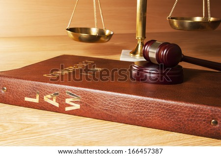 Justice gavel on Law book with scales of Justice in the background - stock photo