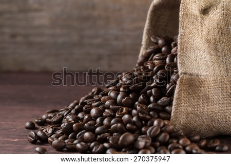 jute bag full of roasted coffee beans and scattered on a wooden table - stock photo