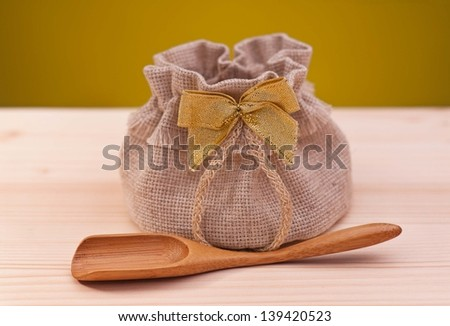 Jute sack with wooden spoon on a wooden surface over dark yellow background - stock photo