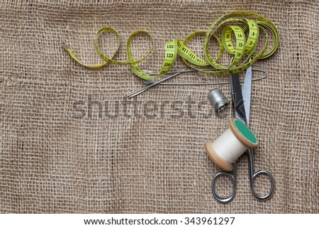 Jute textile cloth with scissors, needle, thread spools for home made embroidery, needlework and tailoring. - stock photo