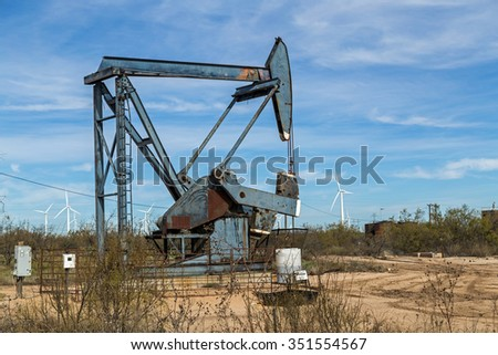 Juxtaposed Oil Well and Wind Turbines.  Energy Resources co-existing. - stock photo
