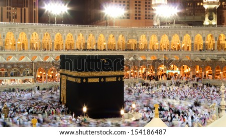 Kaaba in Mecca, Saudi Arabia. Muslim pilgrims, from all around the World, revolving around at night. - stock photo