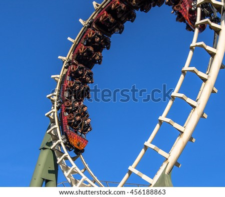 KAATSHEUVEL/THE NETHERLANDS - OCTOBER 31th, 2015:  People enjoying an exhilerating rollercoaster ride at Efteling theme park, against blue sky - stock photo
