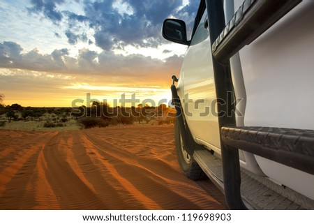 Kalahari sundown with safari suv - stock photo