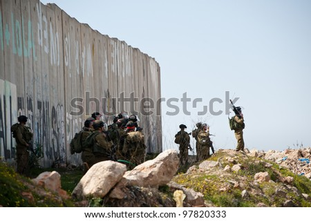 KALANDIA, OCCUPIED PALESTINIAN TERRITORIES - MARCH 8: Heavily armed Israeli soldiers stand near the separation wall at the Kalandia checkpoint during demonstrations  on March 8, 2012. - stock photo