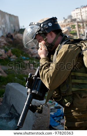 KALANDIA, OCCUPIED PALESTINIAN TERRITORIES - MARCH 8:Israeli soldiers are overcome by the effects of their own tear gas during protests against the occupation of Palestine on March 8, 2012 in Kalandia - stock photo