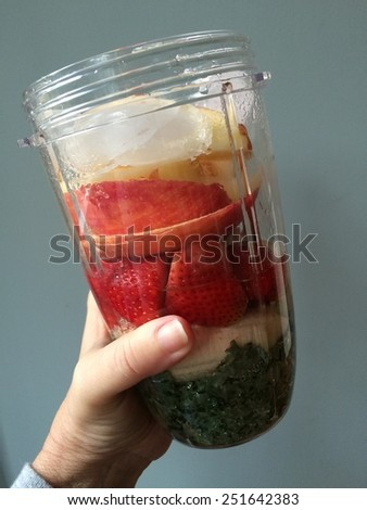 Kale, bananas, strawberries and apples in a cup ready to be blended into a fresh fruit smoothie  - stock photo
