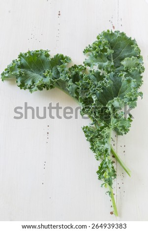 Kale leaves on a cream colored wooden background. - stock photo