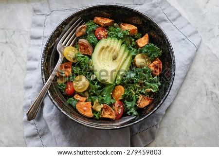 Kale, roasted yams and avocado salad on stone background - stock photo