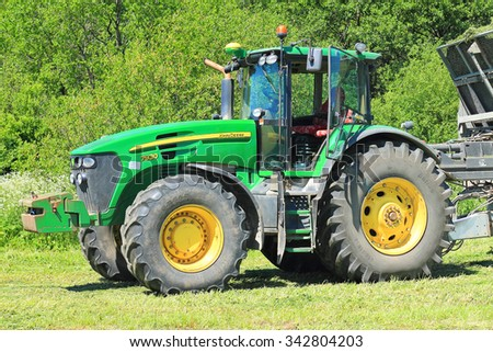 KALININGRAD REGION, RUSSIA - JUNE 11, 2015: The American John Deere 7930 tractor in a sunny day against green foliage - stock photo
