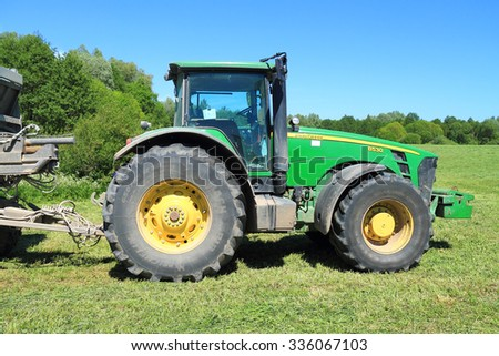 KALININGRAD REGION, RUSSIA - JUNE 11, 2015: The wheel John Deere 8530 tractor on the edge of a field at the wood - stock photo