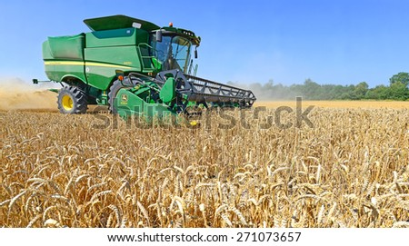 Kalush, Ukraine - AUGUST 11: Modern John Deere combine harvesting grain in the field near the town Kalush, Western Ukraine August 11, 2013  - stock photo