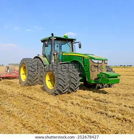 Kalush, Ukraine - August 4: Modern John Deere tractor in the field near the town Kalush, Western Ukraine August 4, 2014 - stock photo