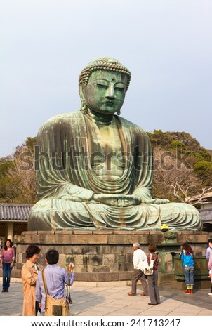 KAMAKURA, JAPAN - MARCH 10: Tourists are looking at a statue of Great Buddha on March 10, 2013 in Kamakura, Japan. With a height of 13 meters, it is the second tallest bronze Buddha statue in Japan. - stock photo