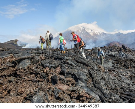 KAMCHATKA, RUSSIA - AUGUST 28, 2013: Tourists go on a route through the active lava flow from a new crater on the slopes of volcanoes Tolbachik, on background volcano Ostry Tolbachik - stock photo
