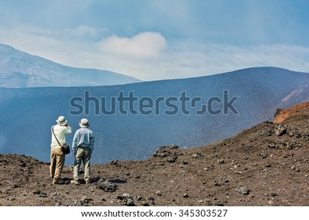 KAMCHATKA, RUSSIA - AUGUST 28, 2013: Tourists go on a route through the active lava flow from a new crater on the slopes of volcanoes Tolbachik - stock photo