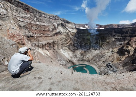 KAMCHATKA, RUSSIA - JULY 21, 2013: Tourist in the crater active Gorely Volcano shoot of the volcano acting fumarole and crater lake. Russia, Far East, Kamchatka Peninsula. - stock photo