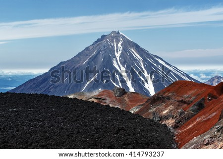 Kamchatka volcanic landscape: view to top of cone of Koryaksky Volcano from scenery active crater of Avacha Volcano on sunny day and blue sky. Russian Far East, Avachinsky-Koryaksky Group of Volcanoes - stock photo
