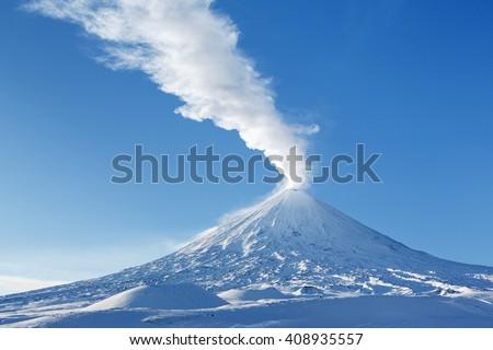 Kamchatka: winter view of eruption active Klyuchevskoy Volcano (Klyuchevskaya Sopka) - emission from crater of volcano plume of steam, gas and ashes. Russia, Klyuchevskaya Group of Volcanoes. - stock photo
