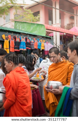 Kanchanaburi, Thailand - DECEMBER 11, 20115: Buddhists are offering food to monks in the morning in Sangkhlaburi, Kanchanaburi, Thailand. - stock photo