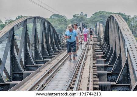KANCHANABURI, THAILAND � FEBRUARY 2: Tourists walk the bridge on the river Kwai in Kanchanaburi, Thailand on February 2, 2009. The bridge is famous due to a movie and its history in WW2. - stock photo