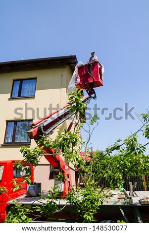 KANIOW, POLAND - JULY 10: The worker repairs and paints the roof on July 10, 2013 in Kaniow, Poland.  Cherry-picker is used to hoist the builder safely. - stock photo