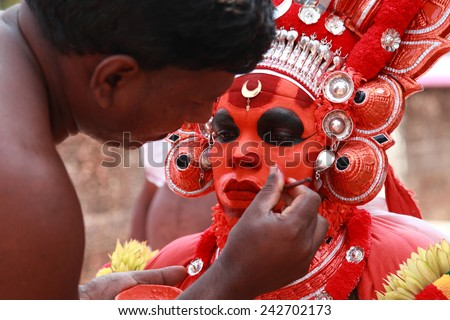 KANNUR - JAN 05: A Theyyam artist does make up during the festival at Kadannappalli Muchilot Bhagavati temple on January 05, 2015 in Kannur, India.Theyyam is a ritualistic folk art form of Kerala - stock photo