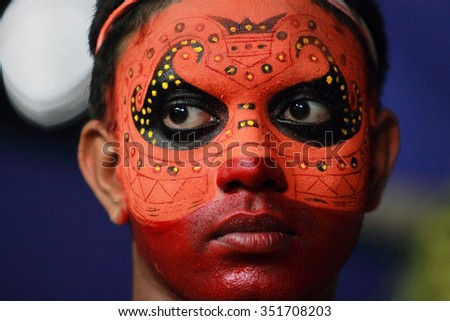 KANNUR - JAN 20: A Theyyam artist looks while performing in the festival at Cherukunnu Puthiya Bhagavati temple on January 20, 2015 in Kannur, India.Theyyam is a ritualistic folk art form of Kerala - stock photo