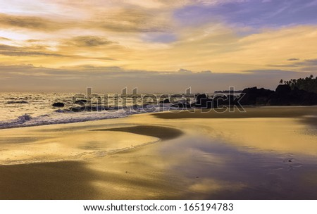 Kannur, Kerala, India. Sunset along the sandy beach at Thottada, 10 km south of Kannur, and overlooking the Arabian Sea and laterite rocks on a calm evening. - stock photo