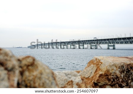 Kansai International Airport is connected only by the Sky Gate Bridge R, a road / railroad bridge to Rinku Town and the mainland. The bridge was given the name Sky Gate Bridge R - stock photo