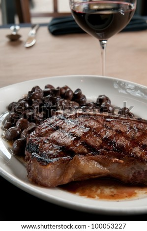 Kansas City strip steak with merlot button mushrooms - stock photo