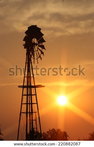 Kansas Windmill Sunset with clouds and trees - stock photo