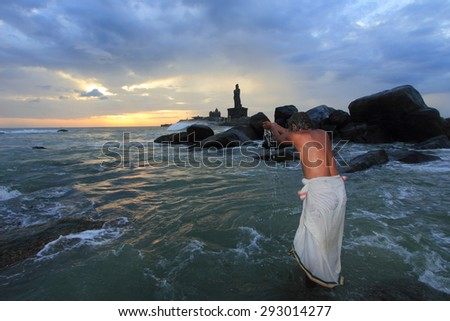 KANYAKUMARI, INDIA - JUL 25:An unidentified Sadhu salutes the sun during sun rise on July 25, 2012 in Kanyakumari,Tamil Nadu, India. Kanyakumari is the southern most tip popular for Hindu pilgrimage. - stock photo