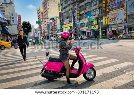 KAOHSIUNG CITY, TAIWAN - JAN 18, 2015: An unidentified scooter rider stop at a traffic junction in Kaohsiung City, Taiwan. Taiwan has 15 million registered scooters. - stock photo