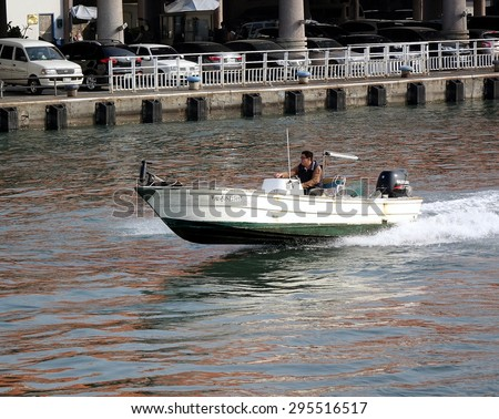 KAOHSIUNG, TAIWAN -- JANUARY 1, 2015: A motorized fishing boat enters the Gushan Marina in high speed. - stock photo