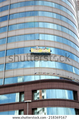 KAOHSIUNG, TAIWAN -- JUNE 27, 2014: Two unidentified workers perform the dangerous task of washing the windows of an office tower - stock photo