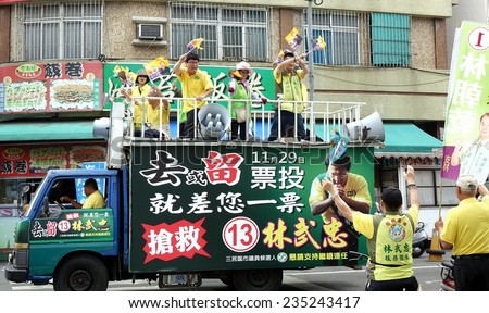 KAOHSIUNG, TAIWAN -- NOVEMBER 28, 2014: Supporters of city council candidate  Lin Low Chung parade through the streets in the run up to the local elections.  - stock photo