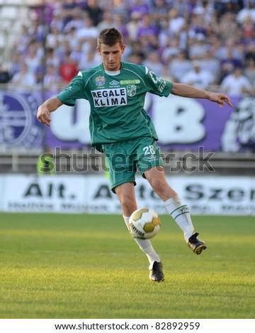 KAPOSVAR, HUNGARY - AUGUST 14: Gabor Janvari (in green) in action at a Hungarian National Championship soccer game - Kaposvar (green) vs Ujpest (white) on August 14, 2011 in Kaposvar, Hungary. - stock photo
