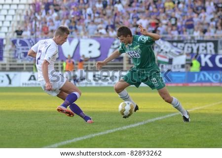 KAPOSVAR, HUNGARY - AUGUST 14: Gabor Janvari (in green 28) in action at a Hungarian National Championship soccer game - Kaposvar (green) vs Ujpest (white) on August 14, 2011 in Kaposvar, Hungary. - stock photo