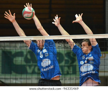 KAPOSVAR, HUNGARY - FEBRUARY 23: Karoly Lesznyik (L) in action at a Hungarian volleyball National Championship game Kaposvar (blue) vs. Csepel (deep blue), on February 23, 2012 in Kaposvar, Hungary. - stock photo