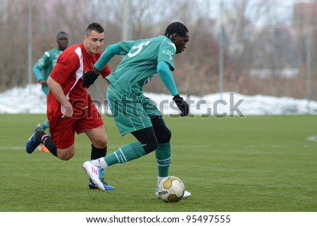 KAPOSVAR, HUNGARY - FEBRUARY 18: Mustapha Diallo (in green) in action at a friendly soccer game Kaposvar (green) vs. Dombovar (red) - February 18, 2012 in Kaposvar, Hungary. - stock photo